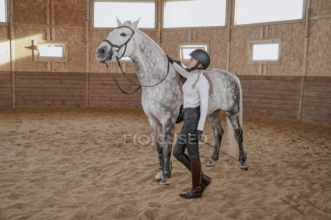 Horsewoman standing with dapple gray horse in round arena — Stock Photo