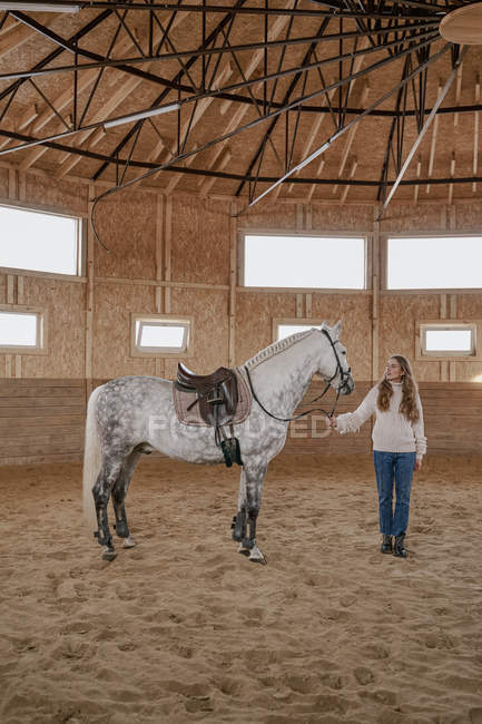 Женщина с серой лошадью с длинным пушистым хвостом ходит по большой арене — стоковое фото
