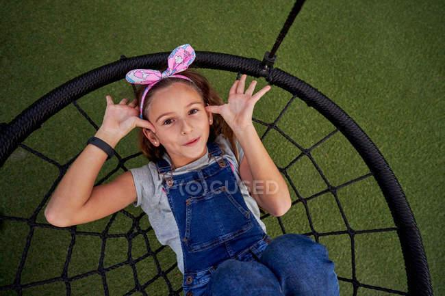 Fröhliches Mädchen hat Spaß auf Korbschaukel — Stockfoto