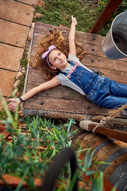 Sorrindo menina inocente deitado no quintal da casa — Fotografia de Stock