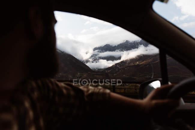 Potentes montañas y vistas al cielo nublado desde la ventana del coche - foto de stock