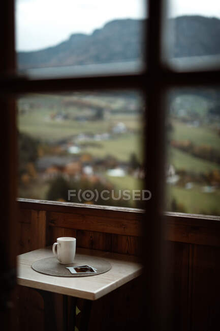 Small table with cup of coffee and photos on terrace on cloudy morning — Stock Photo