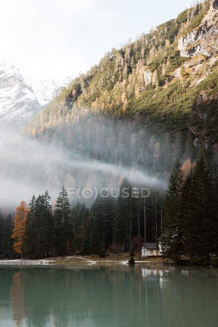 Casa sobre pilotes en el lago cerca de las montañas - foto de stock