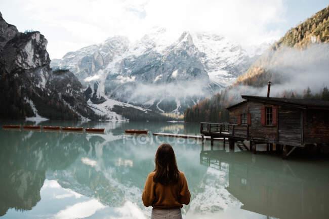 Отдыхающая женщина в повседневной одежде наслаждается видом на озеро и горы — стоковое фото
