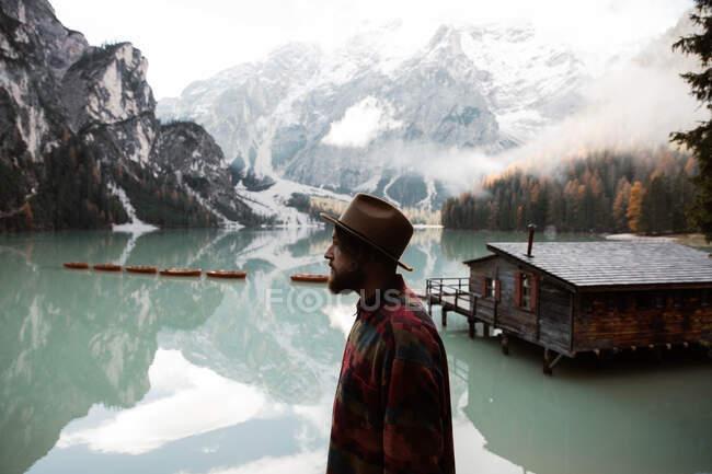 Отдыхающий мужчина в повседневной одежде, наслаждаясь видом на озеро и море — стоковое фото