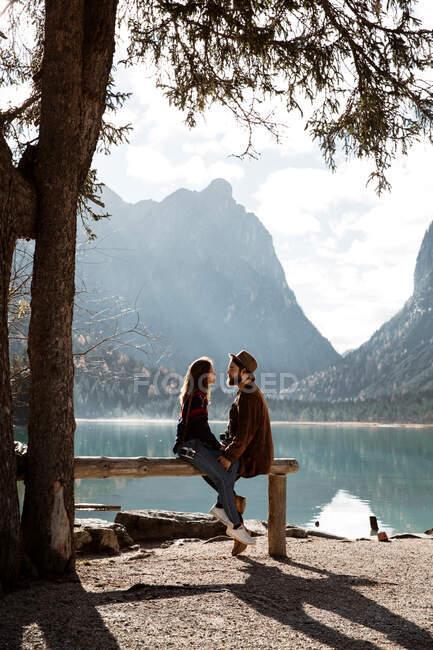 Чоловіки й жінки - мандрівники сидять на огорожі біля озера й гори. — стокове фото