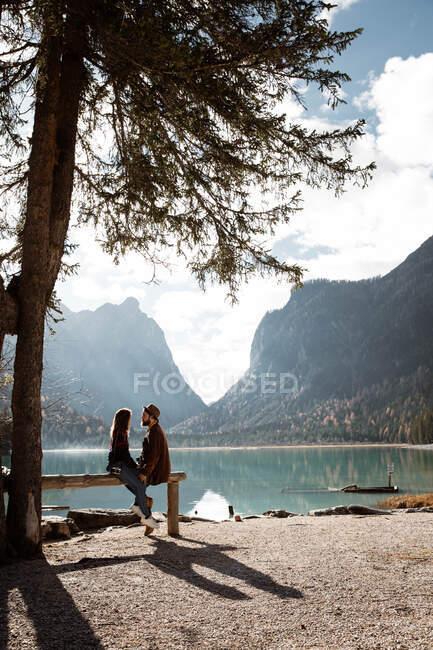 Чоловіки і жінки, які подорожують, сидять на паркані біля озера й гір. — стокове фото