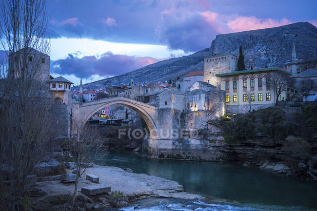 Wonderful scenery of tranquil turquoise river against historical district of picturesque city Mostar with medieval bridge and old buildings at foot of mountain under colorful cloudy sky during sunrise in Federation of Bosnia and Herzegovina — Stock Photo