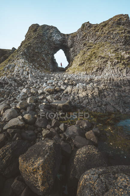 Side view of female in warm outfit standing on cliff edge within cave in harbour of Northern Ireland looking away into sea — Stock Photo