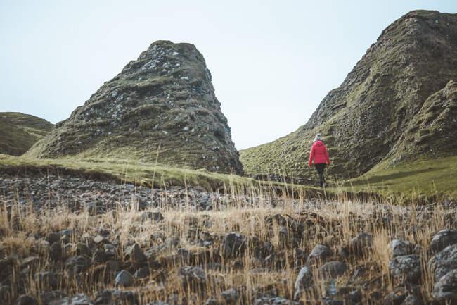 Anonymous woman enjoying amazing scenic landscape of Northern Ireland during travel while walking on rocky ground — Stock Photo