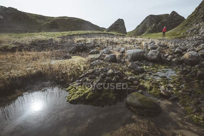 Anonymous woman enjoying amazing scenic landscape of Northern Ireland during travel while walking near fast shallow river flowing to waters of rocky shore — Stock Photo