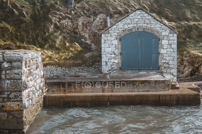 Ancient stone building with doors on picturesque pier of Ballintoy harbour on rocks background — Stock Photo