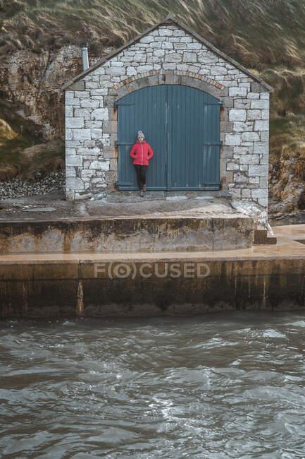 Женщина-туристка в теплой одежде опирается на старинное каменное здание с дверьми, стоя на живописном пирсе гавани Баллинтоя на скальном фоне — стоковое фото