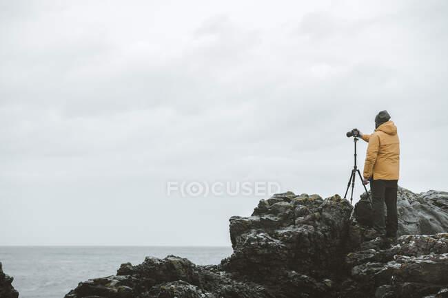 Vista posteriore del viaggiatore di sesso maschile in piedi sulla roccia con fotocamera su treppiede e scattare foto del paesaggio marino in giornata nuvolosa cupa sulla costa dell'Irlanda del Nord — Foto stock