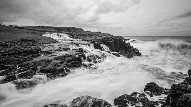 Ondas do mar batendo em rochas e quebrando para baixo a salpicos no dia tempestuoso com nuvens pesadas na costa da Irlanda do Norte — Fotografia de Stock