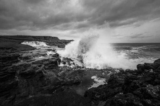 Морські хвилі розбиваються об скелі і розпадаються на брижі в день шторму з важкими хмарами на узбережжі Північної Ірландії. — стокове фото