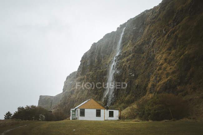 Piccola casa di campagna in legno con pareti bianche e tetto a capanna giallo situata su un prato verde ai piedi della scogliera con cascata contro il cielo grigio nuvoloso in primavera in Irlanda del Nord — Foto stock