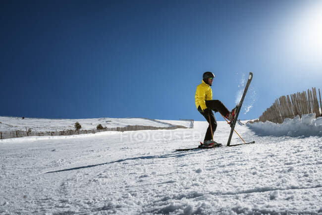 Full body young man in yellow outwear and sunglasses riding skis on snowy mountain slope on sunny winter day on resort — Stock Photo