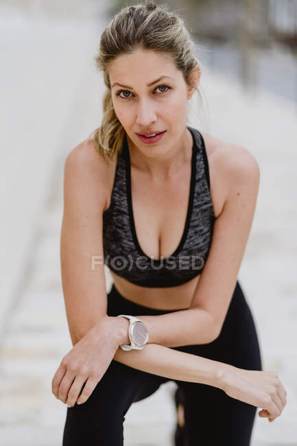Content young female athlete in stylish sportswear with trendy watch leaning hands on knees while looking in camera - foto de stock
