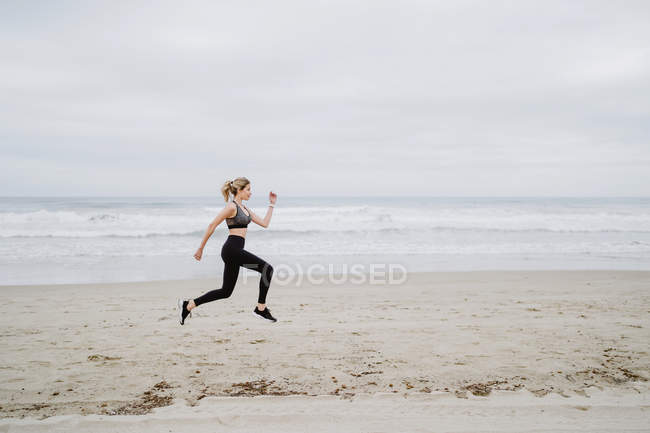Side view of determined female jogger in stylish sportswear and sneakers jumping at empty seashore on cloudy weather — Photo de stock