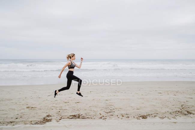 Вид сбоку решительной женщины-бегуньи в стильной одежде и прыгающих на пустом берегу моря в пасмурную погоду — стоковое фото