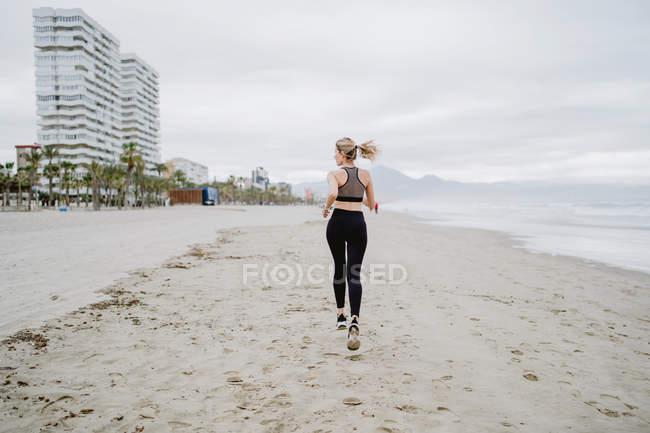 Вид на здоровую женщину, бегущую вдоль тропического пустого побережья в облачную погоду — стоковое фото