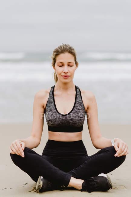 Молодая стройная женщина в черном топе и леггинсы, сидящие в позе лотоса на пляже с закрытыми глазами во время медитации — стоковое фото
