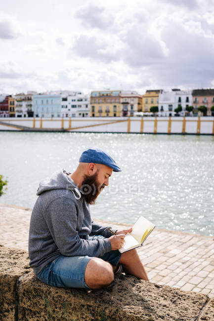 Male art student in casual clothing sitting with crossed legs on rocked fence of quay and drawing sketches in small album — Stock Photo