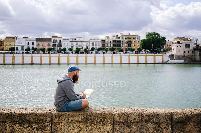 Side view of art student in casual clothing sitting on rocked fence of quay and drawing sketches in small album — Stock Photo