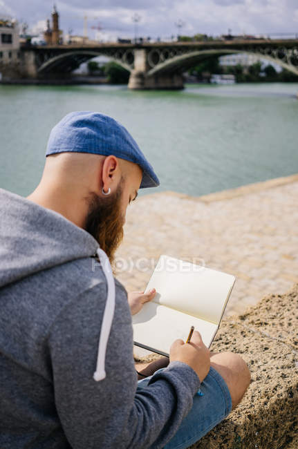 Art student in casual clothing sitting with crossed legs on rocked fence of quay and drawing sketches in small album — Stock Photo