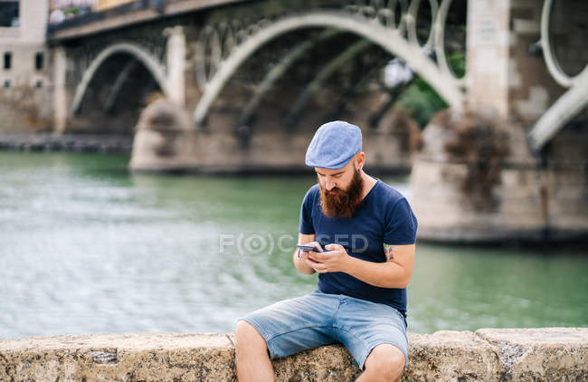 Bearded guy in casual clothing and cap sitting on rocked fence and using smartphone with river on background — Stock Photo
