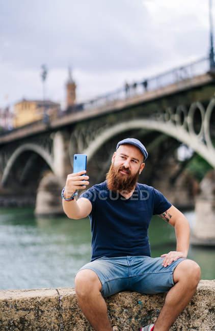 Viaggiatore maschio in abbigliamento casual sorridendo e facendo selfie con smartphone mentre seduto su recinto scosceso di banchina — Foto stock