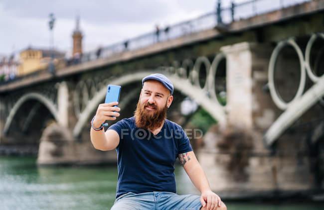 Мандрівник у повсякденному одязі посміхається і робить селфі з смартфона, сидячи на похилому паркані принади — стокове фото