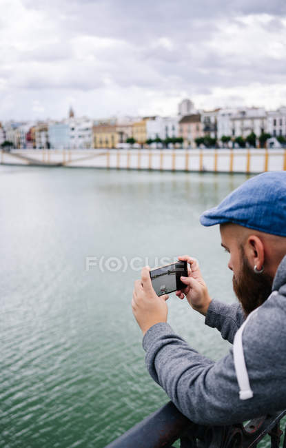 Hipster barbudo masculino em desgaste casual elegante tirar foto do rio com smartphone enquanto está na ponte no cais — Fotografia de Stock