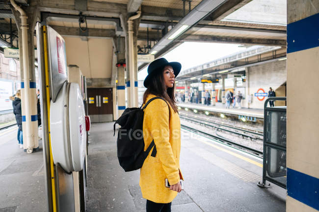 Side view of happy stylish female smiling waiting for a train while standing on platform on station in London, United Kingdom — Stock Photo