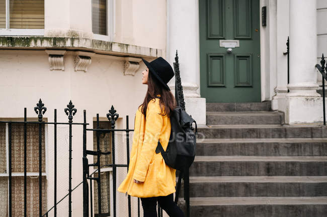 Young woman in trendy yellow coat admiring ornamental buildings while standing on pavement street of London, United Kingdom — Stock Photo