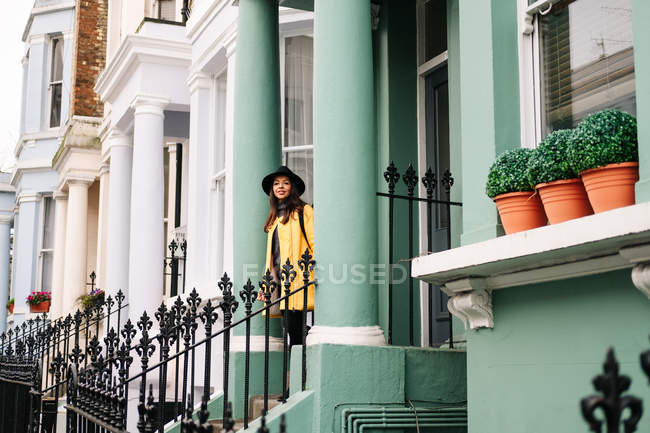 Happy stylish woman in yellow coat and hat smiling while standing in stairs in a house in the streets of London, United Kingdom — Stock Photo
