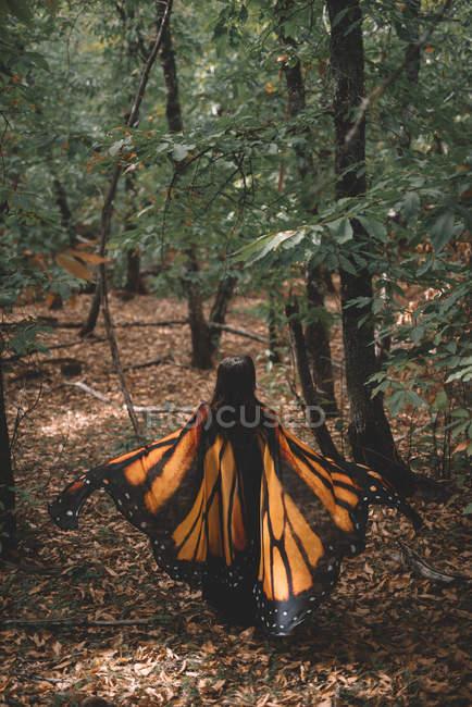 Анонимная молодая женщина в плаще с крыльями бабочки танцует возле деревьев в зеленом лесу — стоковое фото