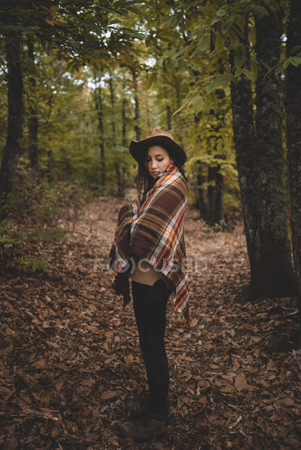 Side view of young woman in hat wrapping in checkered scarf while standing on dry leaves in autumn forest — Stockfoto