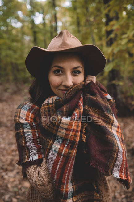Young woman in hat wrapping in checkered scarf while standing on dry leaves in autumn forest looking in camera — Stockfoto