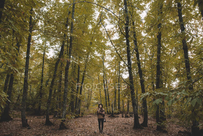 Young woman in hat wrapping in checkered scarf while standing on dry leaves in autumn forest — Stockfoto