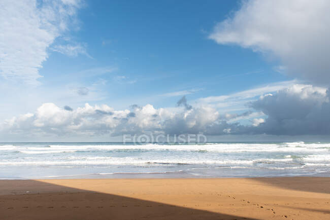 Idyllic empty sandy beach along turquoise ocean with waves and foam under blue cloudy heaven at Zarautz at Spain — Stock Photo