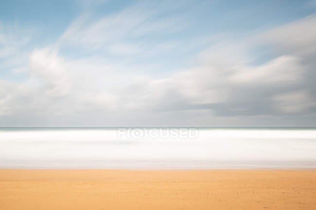 Landscape of lonely sandy seashore with cloudy sky — Stock Photo