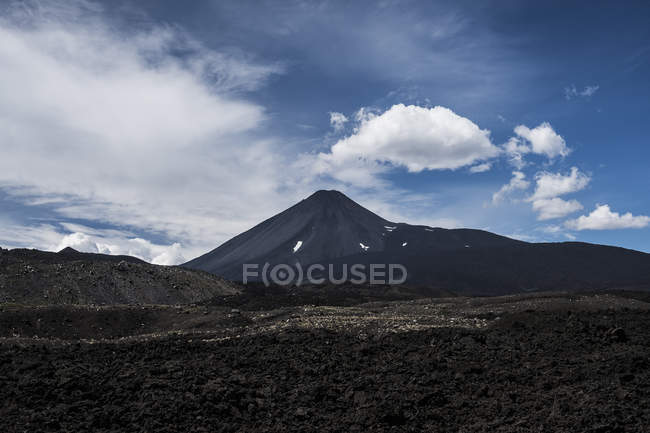Gloomy lonely mountain peak under cloudy sky in rocky valley, Antuco Volcano, Chile — Foto stock