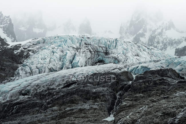 Old shabby stony rocky mountains covered by snow in mysterious haze in Chile — Stock Photo