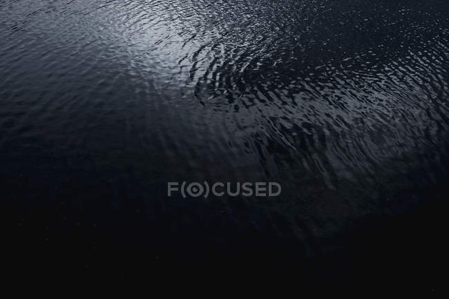 Von oben abstrakte Textur aus dunkelgrauem welligem Wasser, das Wolken in Chili reflektiert — Stockfoto