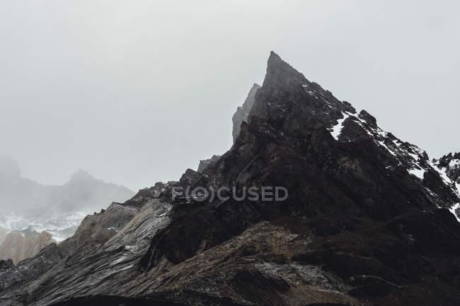 Große steinige Felsen mit Schnee bedeckt in geheimnisvollem Dunst im Torres del Paine Nationalpark, Chile — Stockfoto