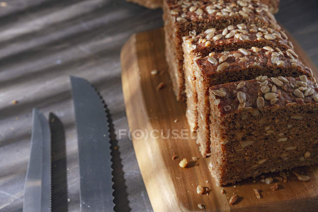 Sliced wholegrain bread on wooden cutting board with knives - foto de stock