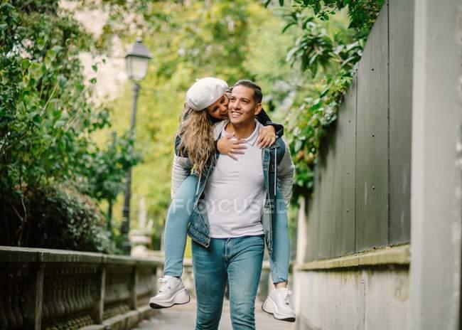 Zufriedene Frau in lässiger Kleidung sitzt auf dem Rücken und küsst zufriedenen Mann zu Fuß auf einer kleinen Gasse mit grünen Pflanzen auf verschwommenem Hintergrund — Stockfoto