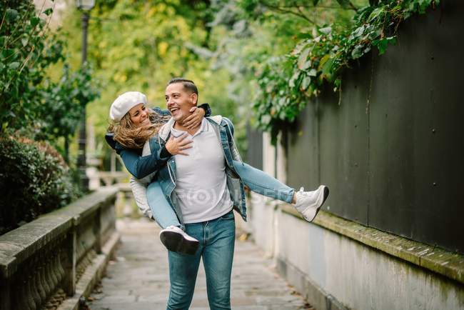 Content woman in casual clothing sitting on back and kissing pleased man walking on small alley with green plants on blurred background — Stock Photo
